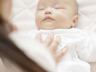 赤ちゃんのお腹の上に母親の手のひら