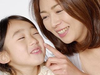 子供の頬を指先で触る母親