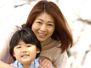 子供を後ろから抱きしめる母親