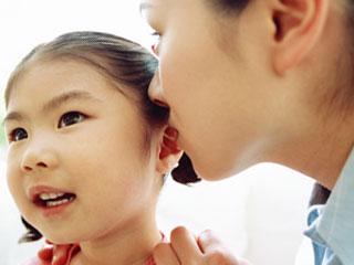 子供の耳に囁く母親