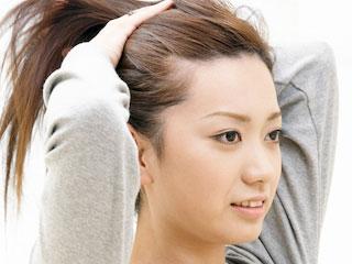 髪を手で束ねる女性