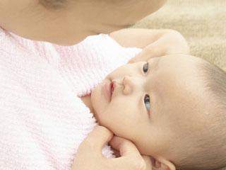 赤ちゃんの口を観察する母親