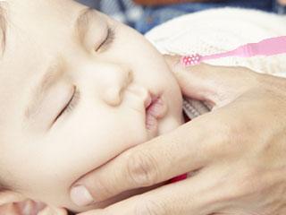 赤ちゃんの口へ歯ブラシ
