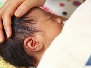 赤ちゃんの頭を触る親の手