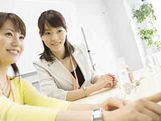 職場で同僚と仕事する女性