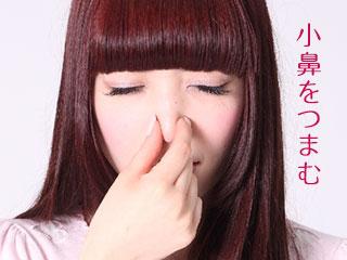 小鼻を摘む女性