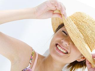 日差しを帽子で防ぐ女性