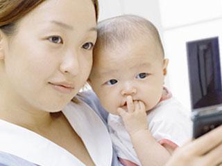 子供を抱きながら自撮りする母親