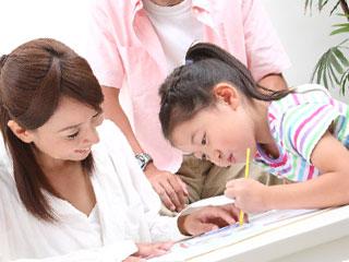 子供の描く絵を見る親