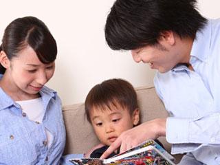 本を子供に見せる両親
