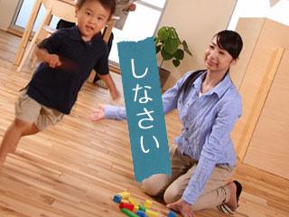 床に散らかる玩具と親子