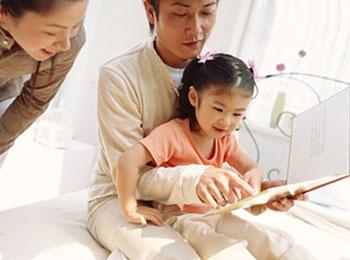 ママとパパに本を読んでもらう子供