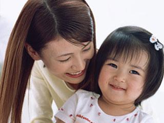 子供に顔を寄せて微笑んでいる母親