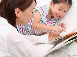 子供と一緒に絵本を読む母親