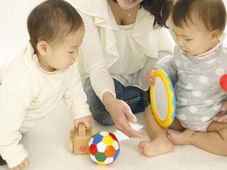 玩具を手に持つ赤ちゃん