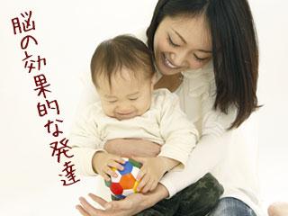 赤ちゃんを抱っこしながらボールで遊ばせる母親