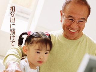祖父と子供が並んでパソコン見ている