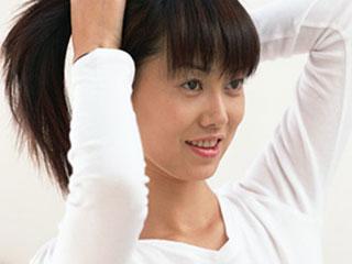 束ねた髪に手をやる女性