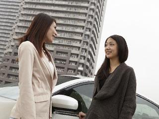 ビルを背景にして車の前で談笑する女性