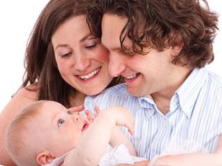 笑顔で赤ちゃんの面倒をみる夫婦