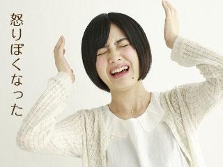 両手を挙げて顔を歪める女性