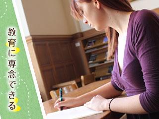 机の上で書き物をする女性教師