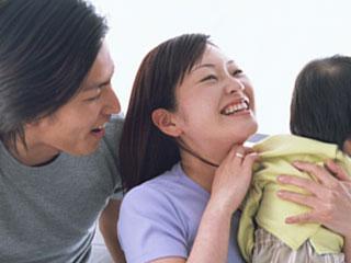 子供を抱く妻に話しかける夫