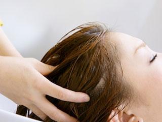洗髪時に頭皮をマッサージされる女性