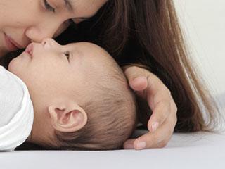 赤ちゃんの頭をなでる母親