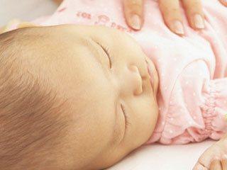 眠る赤ちゃんの体に母親の手