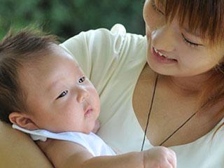 笑顔で赤ちゃんを抱くママ
