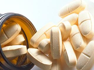 瓶からこぼれ出るサプリメント錠剤