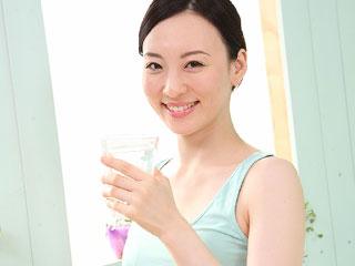 朝、グラスを持つ女性