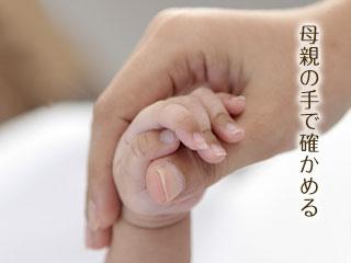 赤ちゃんの手を触る母親の手