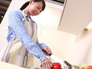 台所で野菜を切る主婦