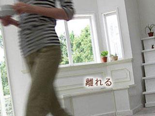 カップを持って居間を横切る女性