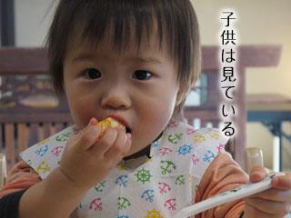 食事をしながら見つめている子供