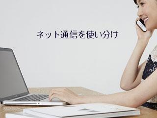 パソコンを見ながらスマホで電話する女性