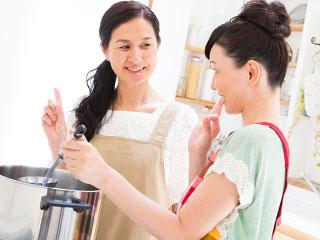 料理しながら義理母と話す女性