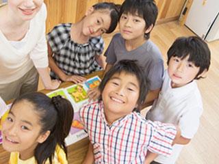 小学生が一緒に絵本を見ている