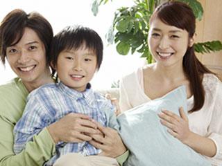子供を膝の上に置いて笑顔の夫