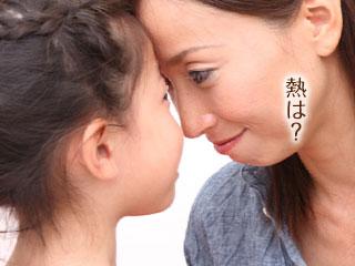 自分の額で子供の熱を計る母親
