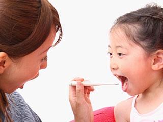 子供の歯磨きを手伝う母親