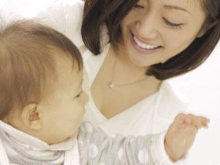 抱いた子供に笑顔を向ける母親
