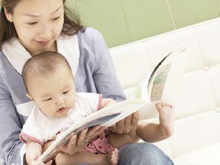 赤ちゃんに絵本を読んで聞かせる母親