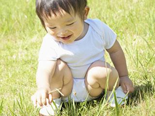 戸外で草を掴んで遊ぶ子供
