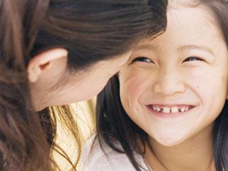 笑顔のこどもの顔を覗きこむ母親