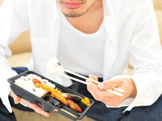 お弁当を食べる夫