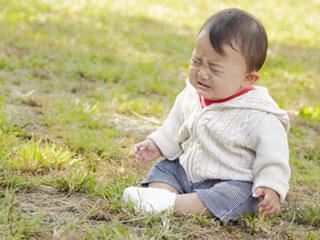 泣いて座り込む赤ちゃん