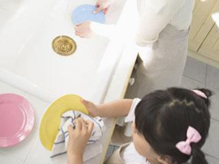 子供が母親の隣で皿を拭いている
